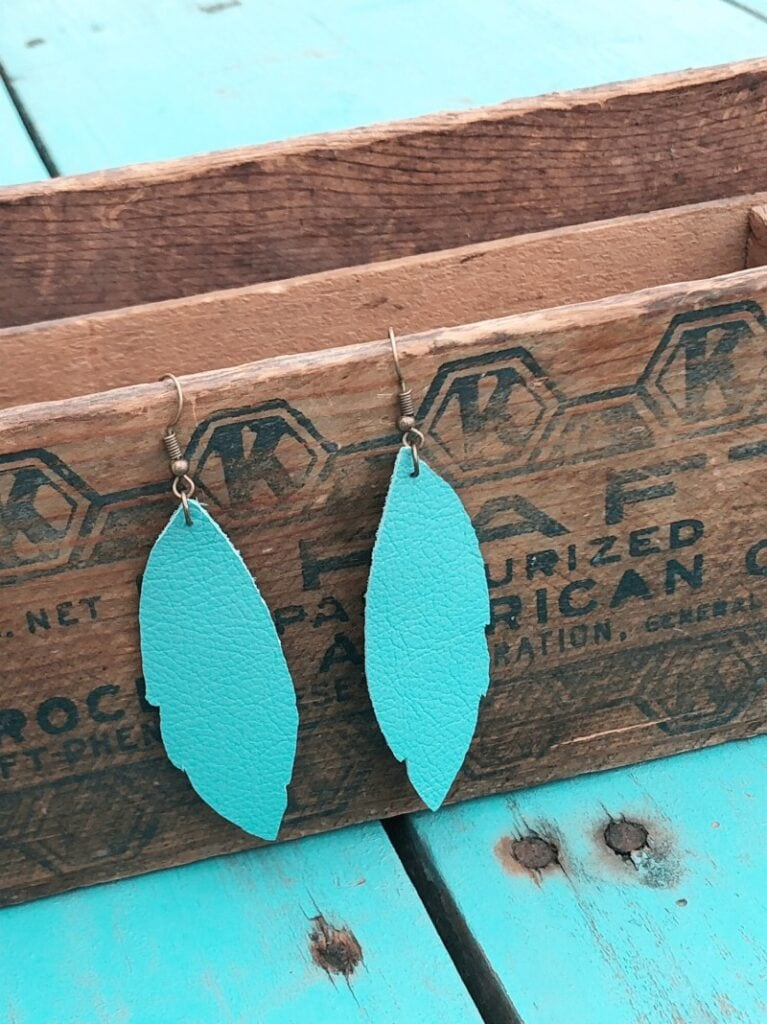 turquoise leather earrings hanging on wooden box