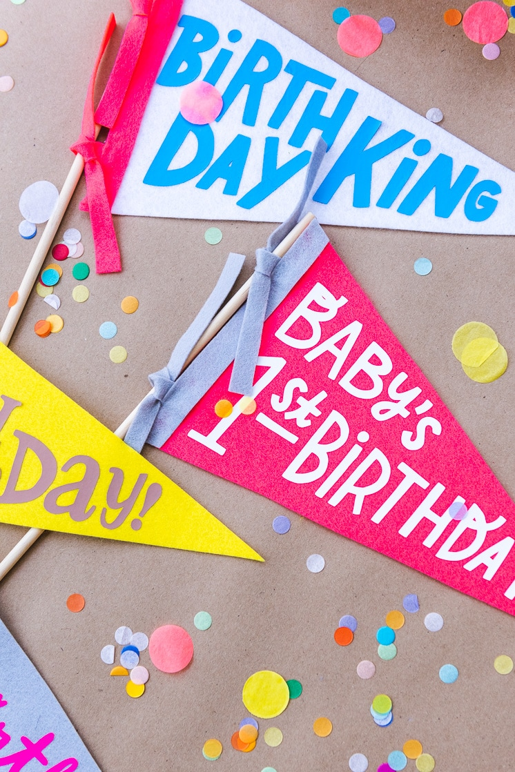 collection of colorful birthday pennants made with felt on a Cricut