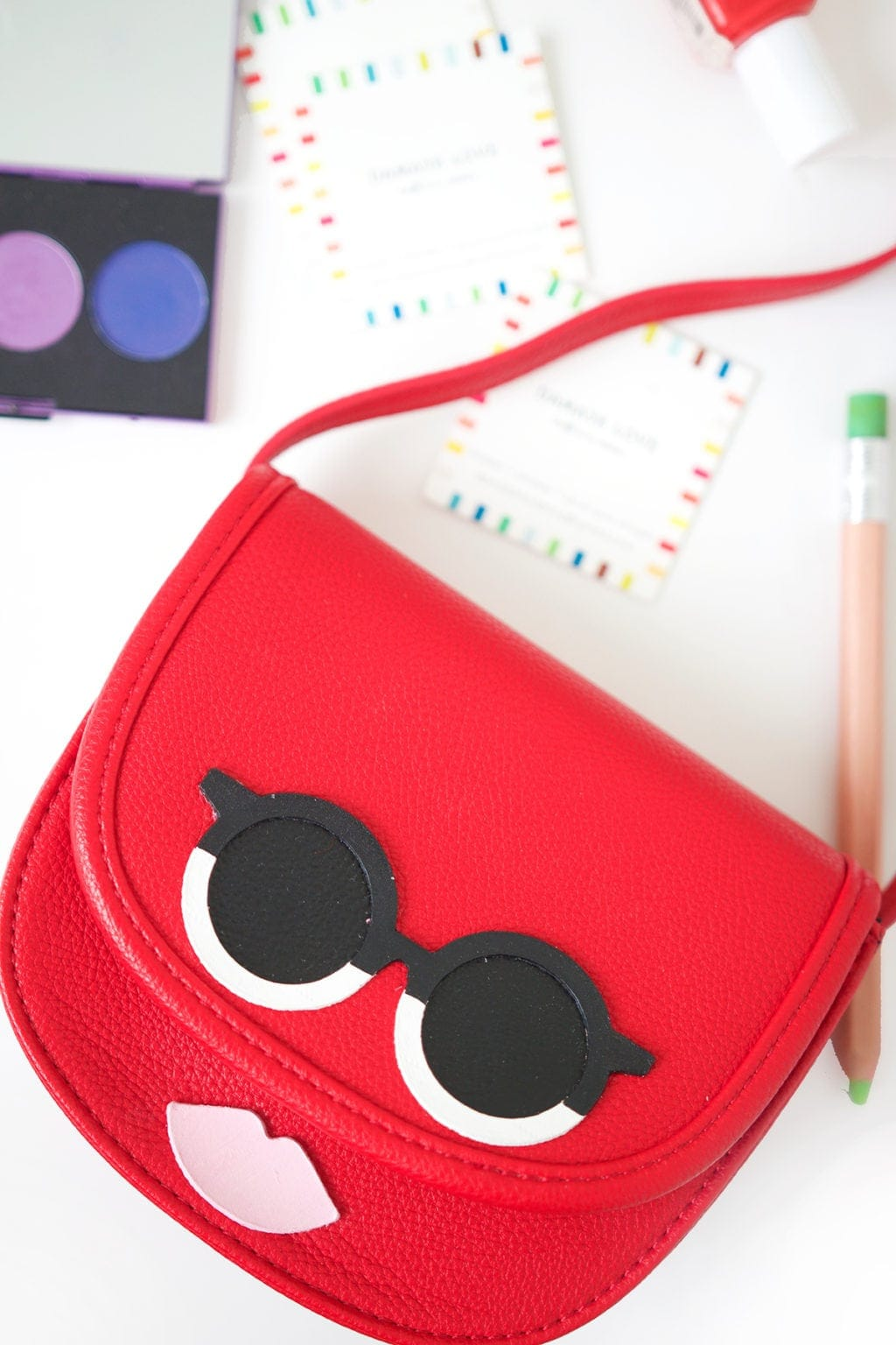 red purse with face added using leather