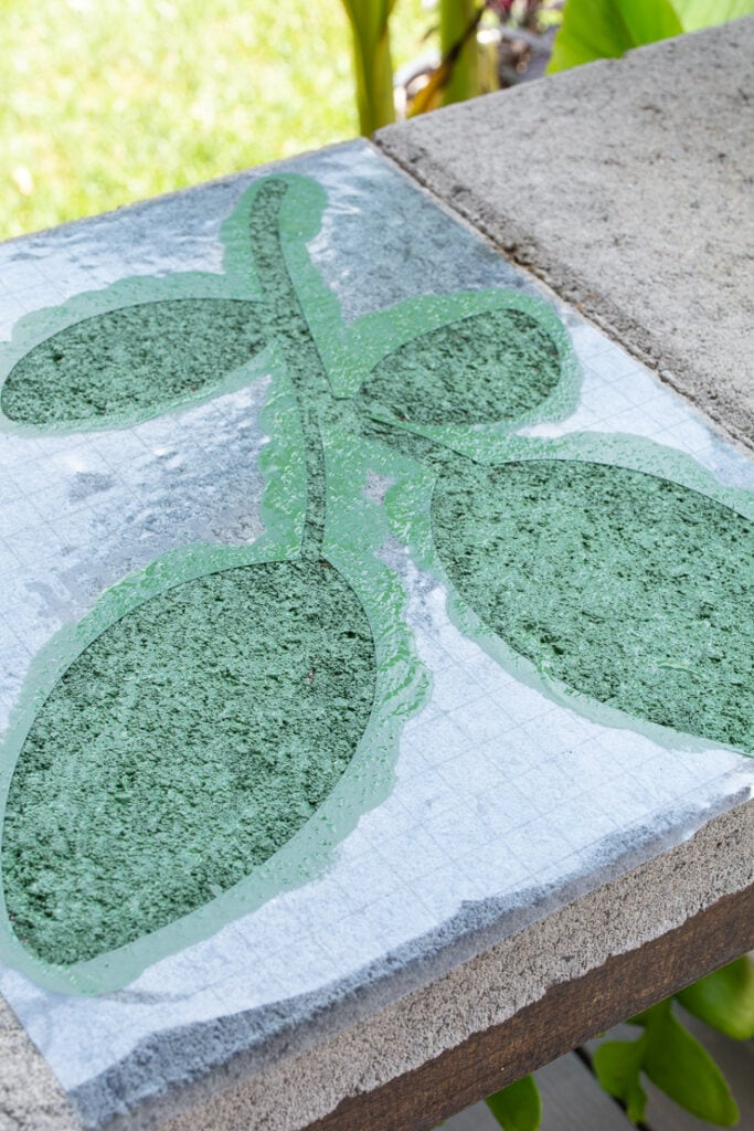 green painted leaf on a concrete paver