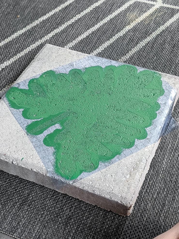 green painted leaf on a concrete paver using a Cricut stencil